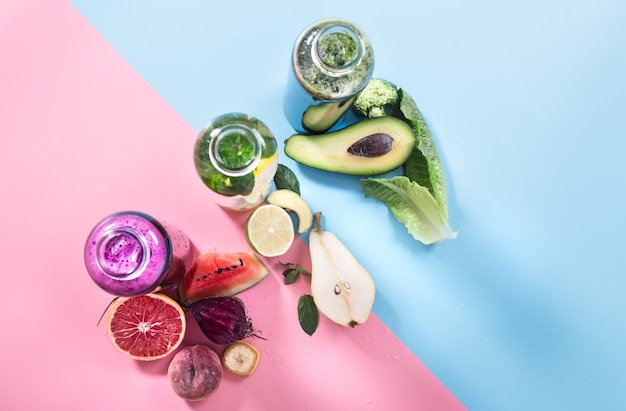 Garrafas de vidro com bebidas naturais em parede colorida