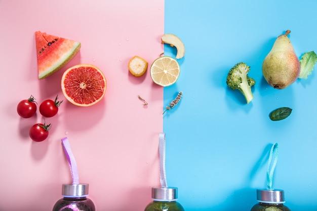 Garrafas de vidro com bebidas naturais em uma parede colorida