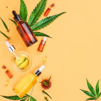 Garrafas de vidro com óleo de cbd, folhas de cânhamo de tintura de thc em um fundo amarelo óleo de cânhamo de cbd para cosméticos