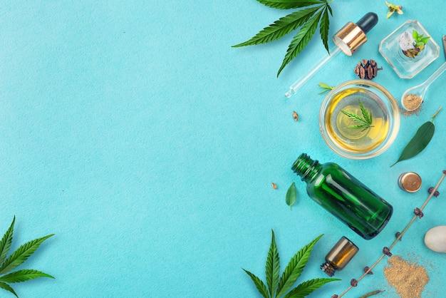 Garrafas de vidro com óleo de cbd, folhas de cânhamo de tintura de thc sobre fundo azul. óleo de cânhamo para cosméticos cbd.