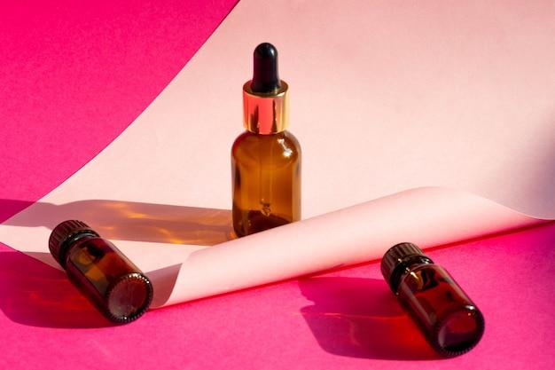 Garrafas de vidro cosméticas em um fundo rosa brilhante com sombras duras. blogger de beleza, conceito de salão de procedimentos. minimalismo. conta-gotas cosmético em um fundo rosa.