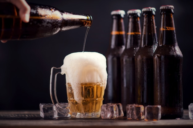 Garrafas de vidro de cerveja com vidro e gelo no fundo escuro