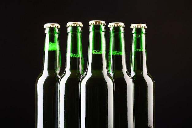 Garrafas de vidro de cerveja gelada estão dispostas no centro