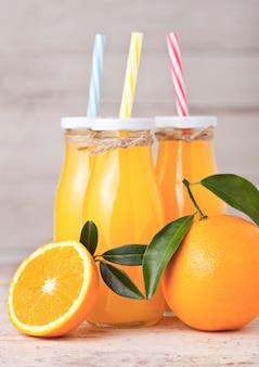Garrafas de vidro de suco de laranja orgânico fresco com laranjas cruas na luz de fundo de madeira
