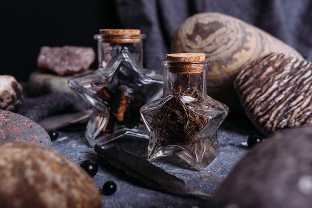 Garrafas de vidro estão cheias de ingredientes mágicos pedras de mesa de bruxas