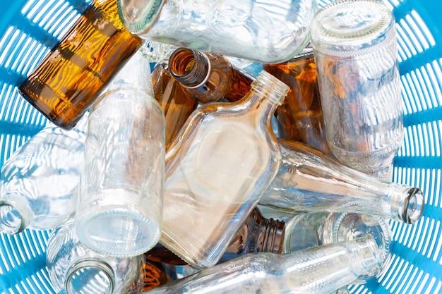 Garrafas de vidro no cesto de lixo.