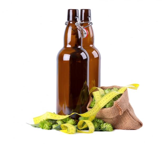 Garrafas de vidro para cerveja kraft com ramo verde fresco de lúpulo e fita métrica amarela, isolado conceito de dieta.