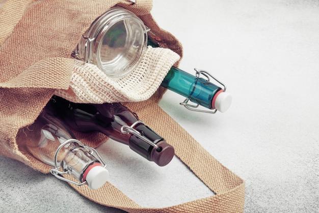 Garrafas de vidro reutilizáveis e frascos em saco de estopa. estilo de vida sustentável. zero resíduos compras conceito