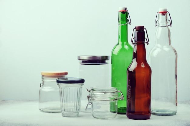 Garrafas de vidro reutilizáveis e frascos na mesa. estilo de vida sustentável. zero resíduos mercearia e conceito de armazenamento