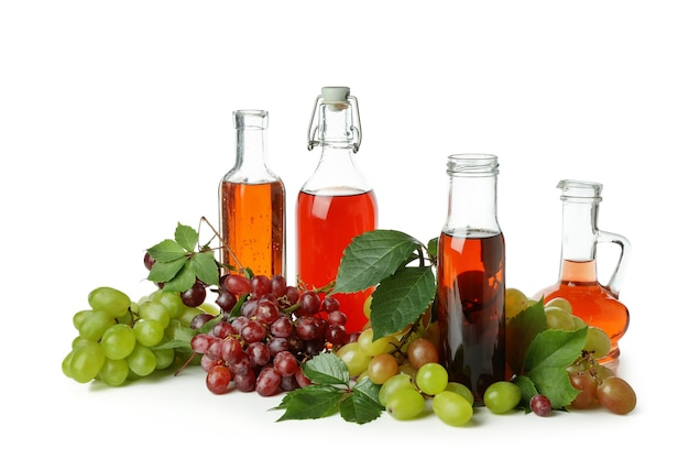 Garrafas de vinagre e uva isoladas no fundo branco
