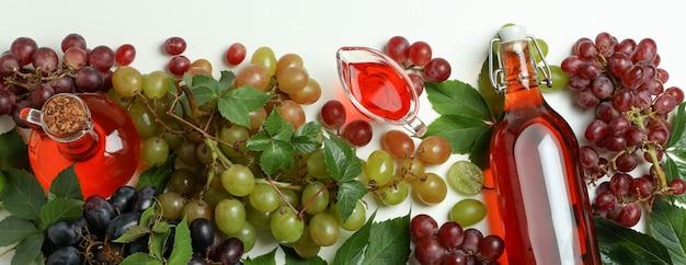 Garrafas de vinagre e uva no fundo branco, vista superior
