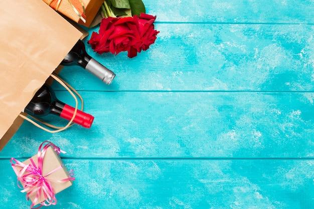 Garrafas de vinho e flores rosas na mesa de madeira