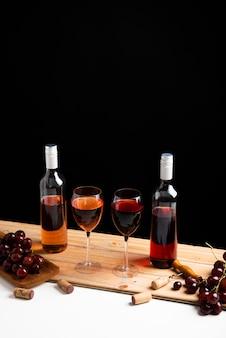 Garrafas de vinho e uvas com fundo preto