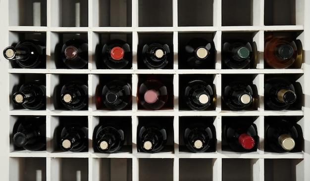 Garrafas de vinho em prateleiras de madeira na adega