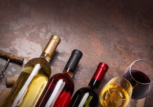 Garrafas de vinho, taças e rolhas na mesa, fundo