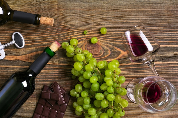 Garrafas de vinho tinto e branco de uva de chocolate e copos sobre mesa de madeira vista com espaço de cópia