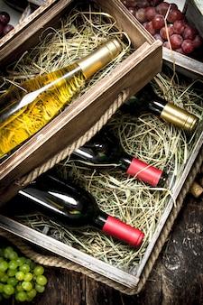 Garrafas de vinho tinto e branco em velhas caixas na mesa de madeira.