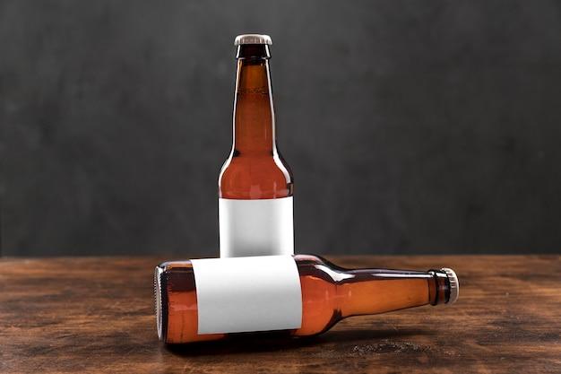 Garrafas de vista frontal com cerveja e adesivos em branco na mesa