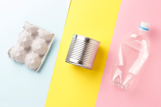 Garrafas do cartão e do plástico, lixo do ferro no fundo amarelo e cor-de-rosa, vista superior.