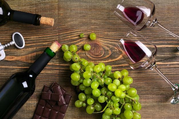Garrafas e copos de vinho chocolate e uvas maduras em fundo de madeira