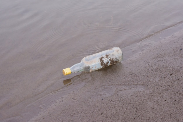 Garrafas e resíduos de lixo na margem de um rio.