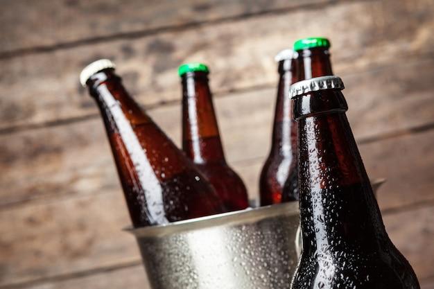 Garrafas geladas de cerveja no balde na madeira