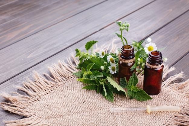 Garrafas marrons com óleos, vegetação e flores mentem no guardanapo marrom