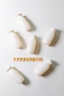 Garrafas pequenas com bebida láctea probióticos e prebióticos em fundo branco. produção com aditivos biologicamente ativos. fermentação e dieta alimentar saudável. bio iogurte com microorganismos úteis.