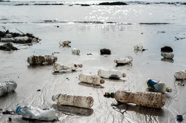 Garrafas plásticas e outros lixos abandonados na praia. poluição ambiental, conceito de problema ecológico.