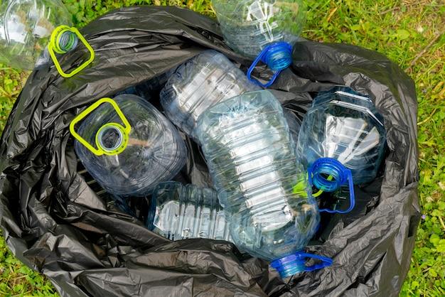 Garrafas plásticas em um saco de lixo plástico preto em um fundo da grama.