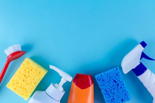 Garrafas, sprays para limpar a casa, esponjas coloridas para lavar a louça e uma escova