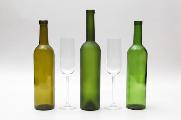 Garrafas vazias e taças de vinho em um branco