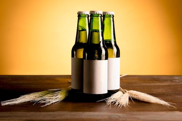 Garrafas verdes de álcool na mesa de madeira