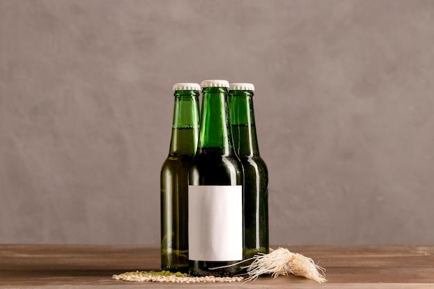 Garrafas verdes em etiqueta branca na mesa de madeira
