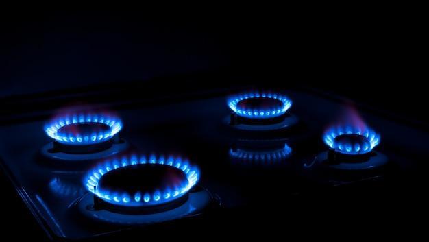 Gás natural queimando chamas azuis em fundo preto
