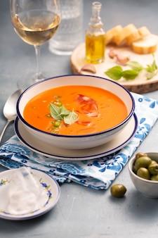 Gaspacho de prato tradicional espanhol feito de tomate, pimentão com pão branco e vinho, azeitonas e uma colher em um prato em um guardanapo azul e branco com um padrão