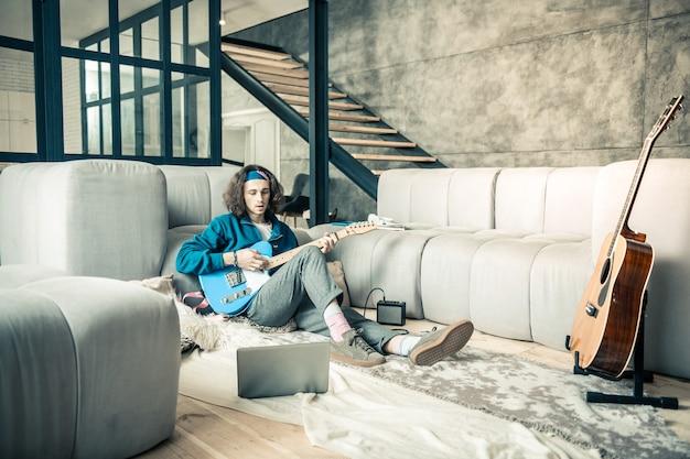 Gastar um tempo tranquilo. homem tranquilo de cabelos escuros sentado no chão de seu apartamento estiloso enquanto se inclina em um sofá cinza