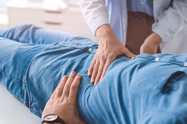 Gastroenterologista examinando homem na clínica