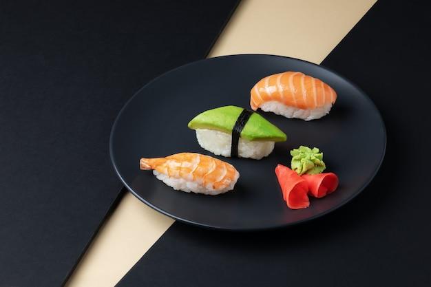 Gastronomia japonesa conjunto de nigiri sushi com salmão, abacate e schrimp em prato preto
