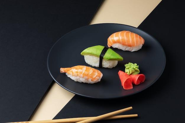 Gastronomia japonesa conjunto de nigiri sushi com salmão e abacate schrimp em prato preto com pauzinhos