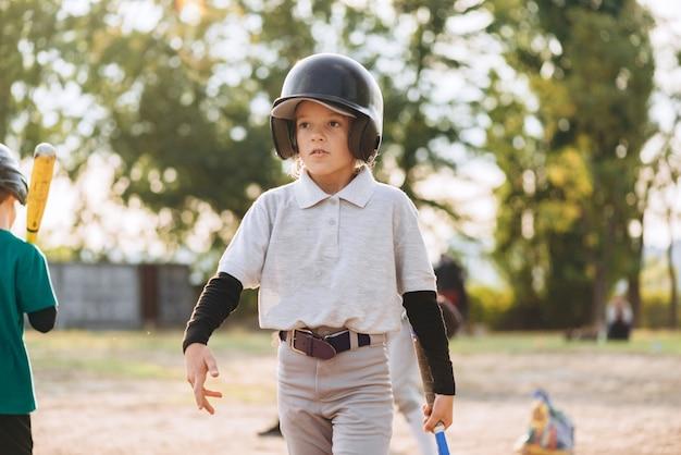 Gata, linda garota de capacete caminha em um campo de beisebol