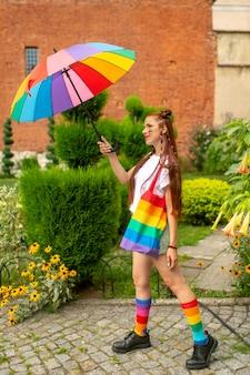 Gata sexy em roupas coloridas e bandeira lgbt nela posando ao ar livre.