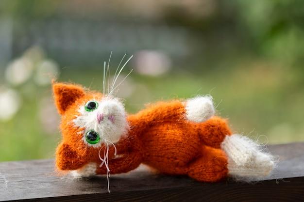 Gatinho de brinquedo de malha, gatinho ruivo com flores na natureza