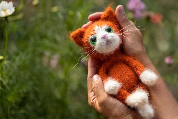 Gatinho de brinquedo de malha, gatinho ruivo nas palmas das mãos de uma mulher