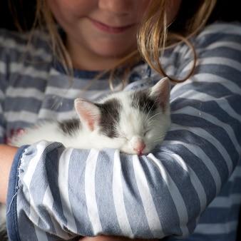 Gatinho dormindo abraçado por menina sorridente