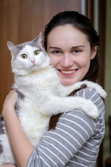 Gato branco cinzento nas mãos de uma jovem garota
