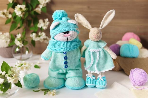 Gato e lebre feitos de fios de lã. brinquedo de pelúcia de malha artesanal sobre uma mesa de madeira.
