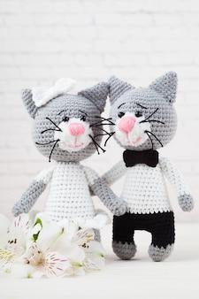 Gatos de malha, casal, brinquedos. feito à mão, amigurumi. fundo branco, cartão postal. faça você mesmo