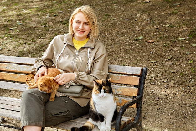 Gatos perdidos de istambul sentam-se no banco perto de uma jovem mulher branca sorridente.