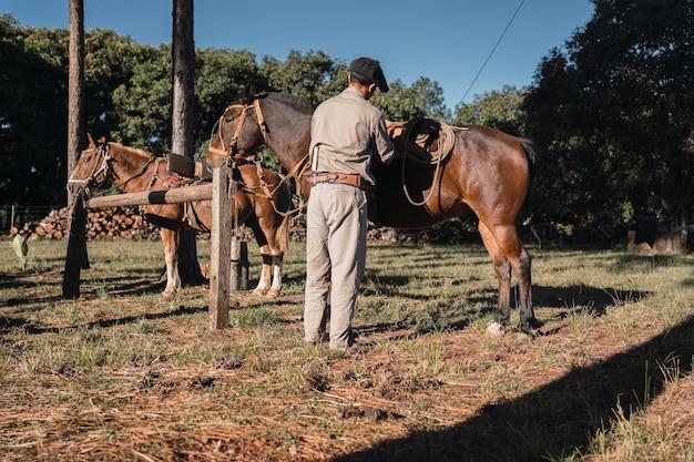 Gaúcho argentino com cavalos em traje de trabalho, com calcinha e boina gaúcha, tradicional cena argentina.